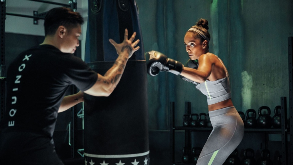 A boxer trains on a heavy bag with the help of a trainer in an Equinox shirt.