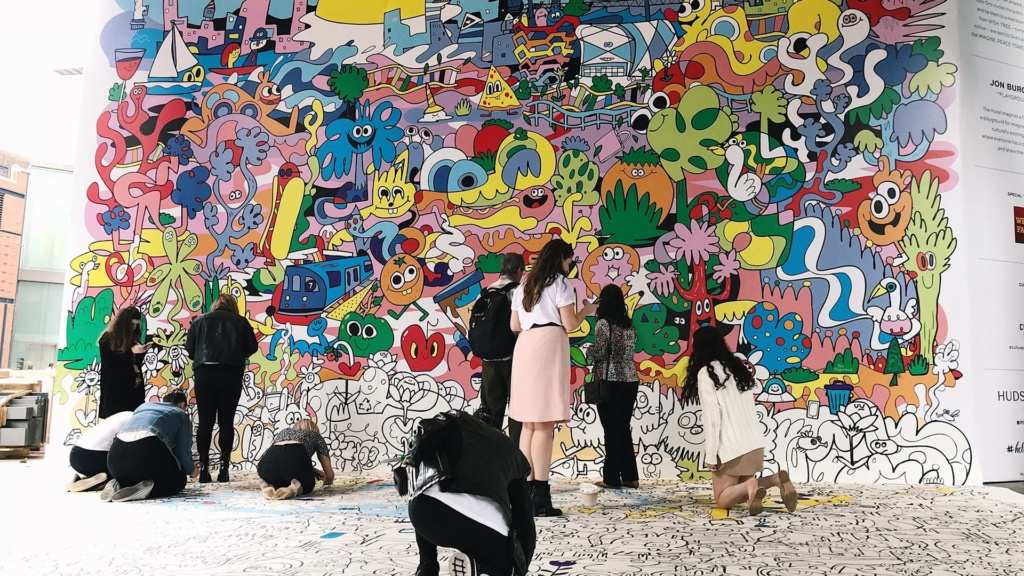 A group of people help add color to a mural outside of 50 Hudson Yards.