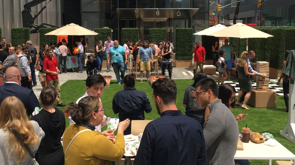 People play Cornhole and Jenga while enjoying the sun on the 50 Hudson Yards campus.