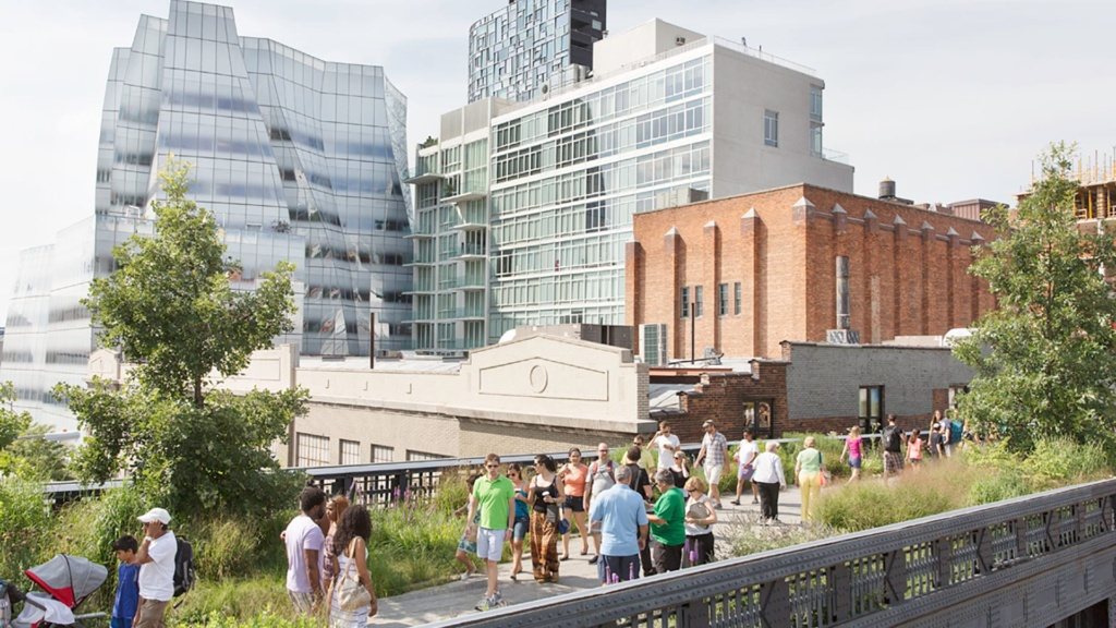 People enjoy the sun while walking along the High Line in NYC.