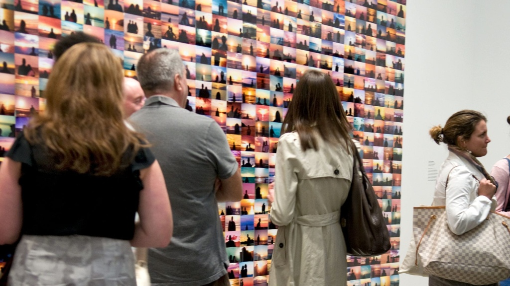 People admire a collage of photographs at a New York art gallery.